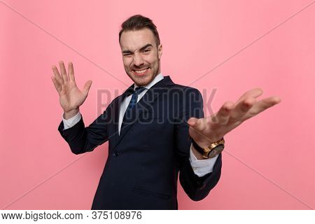 enthusiastic young guy in suit holding hands in the air and presenting, standing on pink background