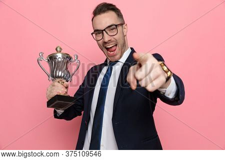 enthusiastic elegant guy in suit wearing glasses, holding silver trophy and pointing finger, laughing and standing on pink background