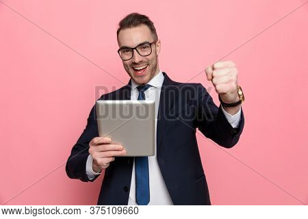 enthusiastic elegant guy in suit wearing glasses, holding tab and reading emails, holding fist in the air and celebrating victory, standing on pink background