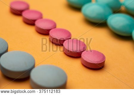 Close Up Of Pills On Orange Background, Concept Of Painkillers Addiction. Lot Of Tablets, Overdose.