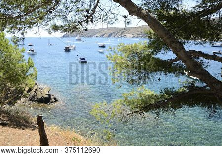 Recreational Ships On The Crystalline Waters In Cadaques Cove, A Coastal Village In The Province Of