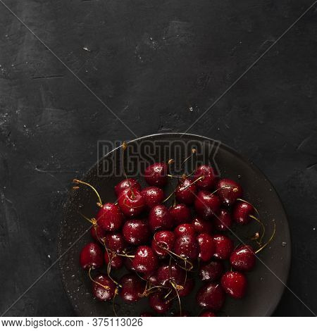 Many Ripe Bright Cherry Berries With Water Drops On Black Plate On Dark Chalkboard Background. Squar