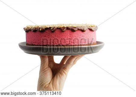 Human Hand Holding Homemade Raspberry Cheesecake Sprinkled With Walnuts Crumbs Isolated On White