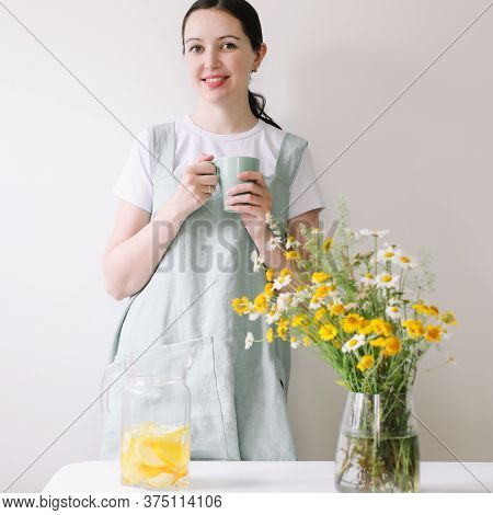 Woman In Linen Apron Drinking Lemonade With Cozy Home Background. Clean Natural Fabric Apron And Flo