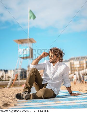 Summer Lifestyle With A Young Dark-haired Caucasian Man With Long Beard, Sunglasses And A White Shir