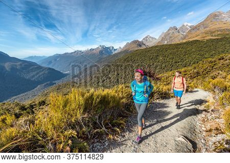 Hiking couple walking on trail at Routeburn Track during sunny day. Male and female hikers are tramping on Key Summit Track. travelling in Fiordland National Park in New Zealand.