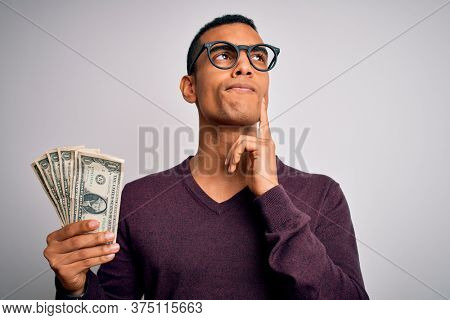 Handsome african american man holding bunch of dollars banknotes over white background serious face thinking about question, very confused idea