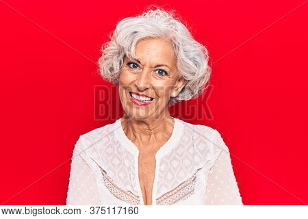 Senior grey-haired woman wearing casual clothes happy face smiling with crossed arms looking at the camera. positive person.