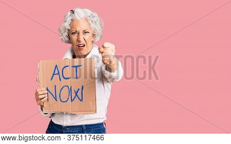 Senior grey-haired woman holding act now banner annoyed and frustrated shouting with anger, yelling crazy with anger and hand raised