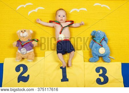 Child Is Standing On A Place Podium In First Place. First Place Winner