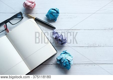 Crumpled Paper Ball And Notepad On Wooden Table.