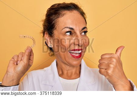Middle age senior dentist woman holding clear aligner for teeth correction pointing and showing with thumb up to the side with happy face smiling