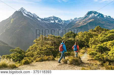 Hiking couple walking on trail at Routeburn Track in New Zealand. Hikers trekking wearing backpacks while tramping on Key Summit Track on vacation at Fiordland National Park, New Zealand.
