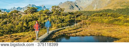 New Zealand Hiking. Panoramic banner of Young hiking couple walking on trail at Routeburn Track during. Hikers carrying backpacks tramping Key Summit Track, Fiordland National Park, New Zealand.