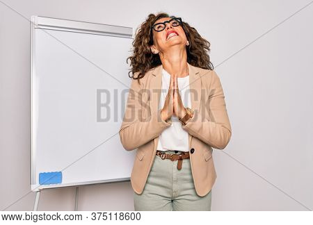 Middle age senior business woman standing on seminar presentation by magnectic blackboard begging and praying with hands together with hope expression on face very emotional and worried. Begging.