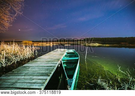 Real Night Sky Stars Above Old Pier With Moored Wooden Fishing Boat. Natural Starry Sky And Countrys