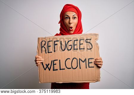 Woman wearing muslim hijab asking for immigration holding welcome refugees message scared in shock with a surprise face, afraid and excited with fear expression