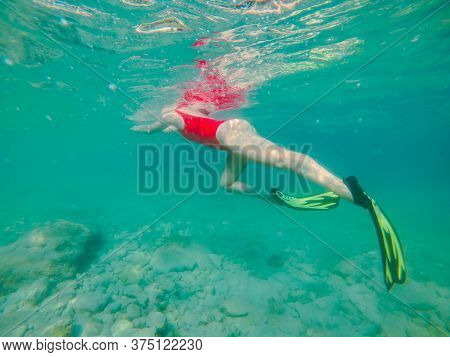 Woman In Red Swimming Suit Underwater With Snorkeling Mask And Flippers