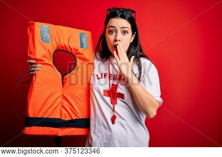 Young lifeguard woman holding rescue lifejacket over red background cover mouth with hand shocked with shame for mistake, expression of fear, scared in silence, secret concept