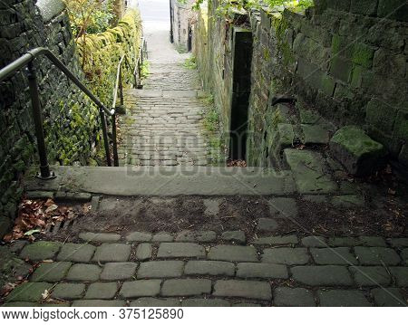 Old Outdoor Stone Steps In Dark Alley With Cobblestones And Moss Growing On The Walls