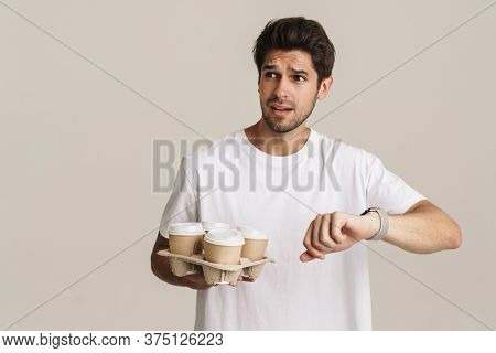 Portrait of scared handsome man looking at wristwatch and holding paper cups isolated over white background