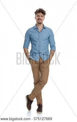 smiling casual guy wearing denim shirt holding hands in pockets, standing isolated on white background, full body