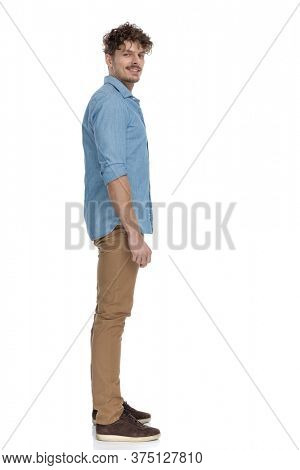happy casual man in denim shirt smiling and waiting in line, isolated on white background, full body