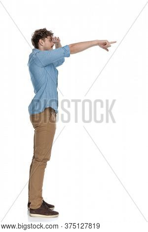 side view of casual man holding hand to forehead trying to see, pointing finger to side and standing isolated on white background, full body