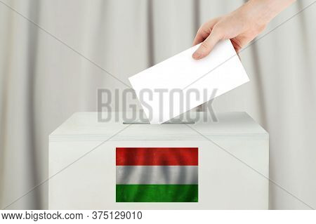 Hungarian Vote Concept. Voter Hand Holding Ballot Paper For Election Vote On Polling Station