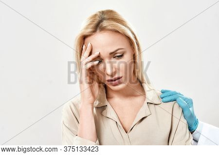 Portrait Of Depressed Young Woman Visiting Doctor. Doctor In Blue Sterile Gloves Supporting And Comf