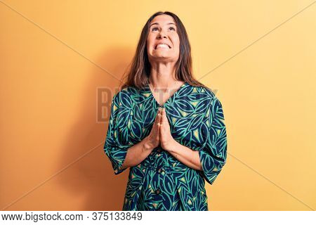 Young beautiful brunette woman wearing casual floral dress standing over yellow background begging and praying with hands together with hope expression on face very emotional and worried. Begging.