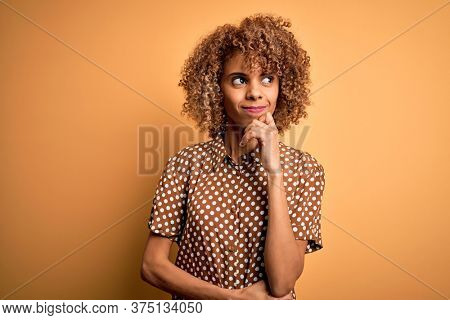 Young beautiful african american woman wearing casual shirt standing over yellow background with hand on chin thinking about question, pensive expression. Smiling with thoughtful face. Doubt concept.