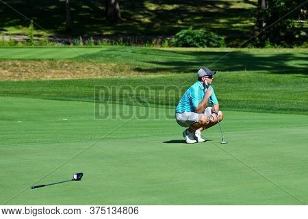 Young Man Looking Over The Green On A Beautiful Golf Course Before Taking His Putt Shot.