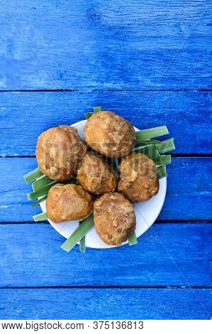 Palm Jaggery In A Plate Isolated Blue Colored Wooden Background In Vertical Orientation