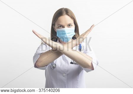 Young Female Caucasian Doctor Woman Wearing Mask And Uniform, Making Stop Sign Gesture, Saying No Is
