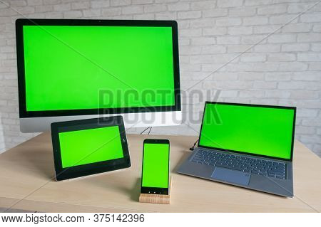 On The Table Are A Computer Laptop Digital Tablet And A Phone With Green Screens On A Brick Wall Bac