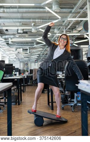 Cheerful Business Woman In Red High Heel Shoes Lost Equilibrium On The Balance Board And Falls. A Fe
