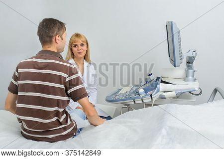 The Lady Ultrasunography Doctor Is Explaining To The Patientat Divice, In Medical Office