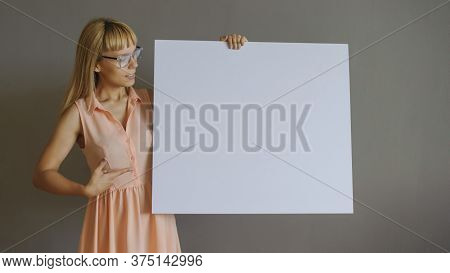A Pretty Blonde Girl With A Whiteboard, Close View, Grey Background