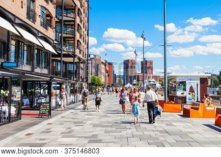 Oslo, Norway - July 20, 2017: Pedestrian Promenade At The Aker Brygge Waterfront In Oslo, Norway. Ak