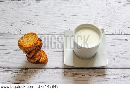 Cup Of Milk And Bread Crumbs On A Wooden Background. Healthy Breakfast.