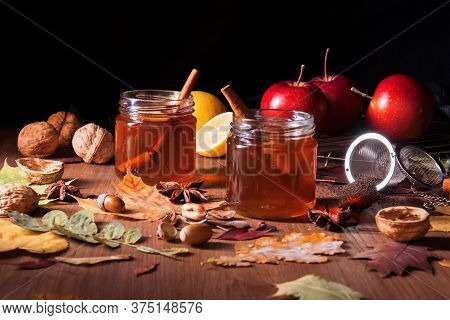 Dark Wooden Table With 2 Glasses Of Tea With Fall, Autumn Decoration And Dark, Black Background. Col