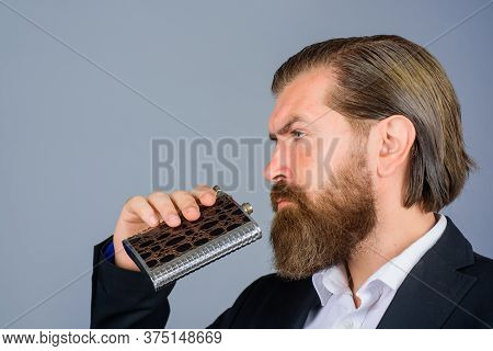 Businessman In Suit With Flask Of Whiskey. Man Drink Whiskey From Bottle. Flat Metal Bottle For Alco