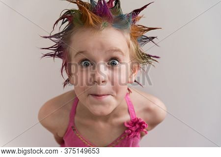 The Child Looks Directly Into The Camera With Large Eyes. A Girl With Multicolored Hair In An Evenin