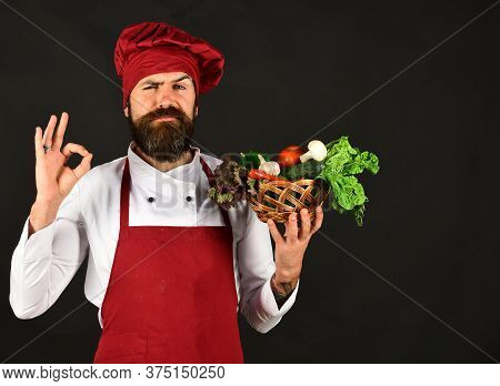Cook With Confused Face In Burgundy Uniform Holds Vegetables