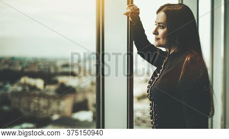 Side View Of A Charming Caucasian Woman Leaning Against The Window Frame And Wistfully Observing Eve