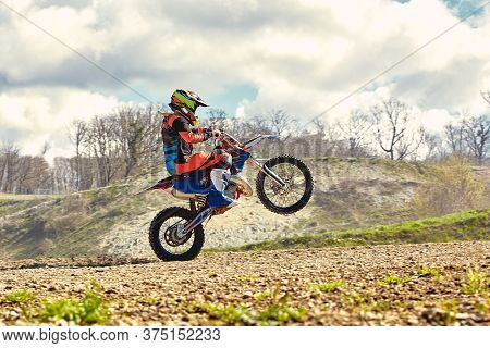 Motocross Driver In Action Accelerating The Motorbike Takes Off And Jumps On Springboard On The Race