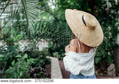 Stylish Summer Accessories. Fashionable Woman Wearing Straw Sun Hat Walking In Tropical Exotic Green