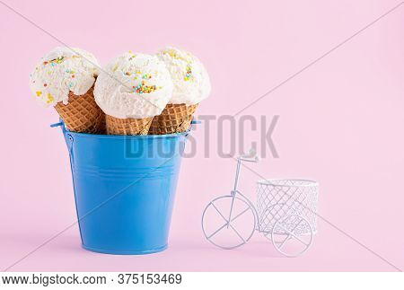 Ice Cream Cones In A Blue Bucket And Small White Bicycle On A Pink Background. A Wafer-style Ice Cre