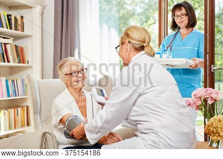 Nurse measures the blood pressure of a senior in assisted living